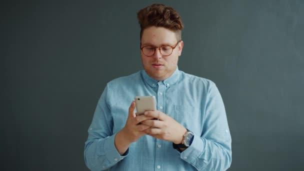 Zpomalený pohyb šťastný muž smskování pomocí smartphone s úsměvem na šedém pozadí