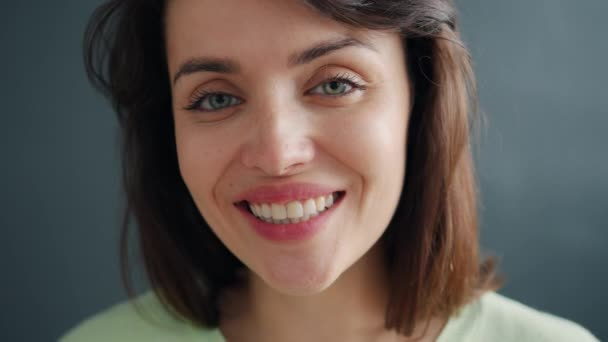 Close-up slow motion portrait of cheerful young lady smiling on dark background