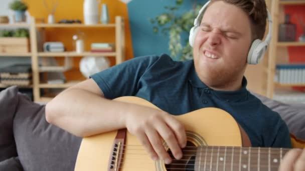 verspielter Typ, der zu Hause Gitarre spielt und Spaß dabei hat, drahtlose Kopfhörer zu tragen