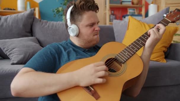 fröhlicher Student spielt Gitarre und hört Musik über Kopfhörer in der Wohnung