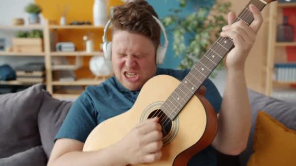 Kreativer Typ mit ausdrucksstarkem Gesicht, der zu Hause mit Kopfhörern Gitarre spielt
