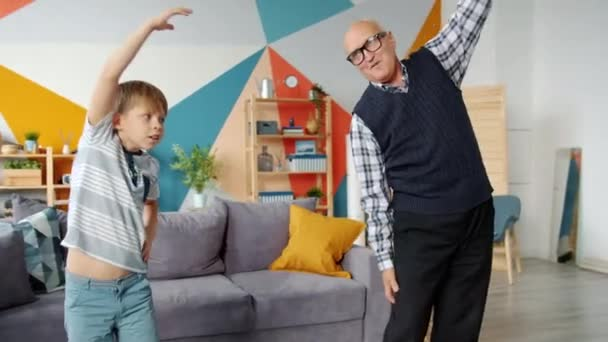 Retired grandfather and cute child do physical exercises together in house