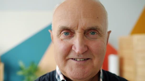 Lassú mozgás az öregember mosolyog nézi kamera otthon színes háttér