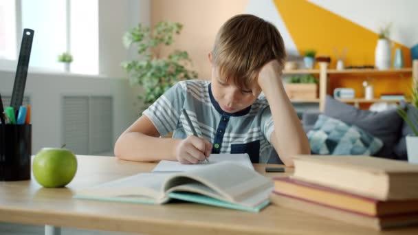 Portrét chytrého kluka, jak doma dělá domácí úkoly a studuje psaní na stole.