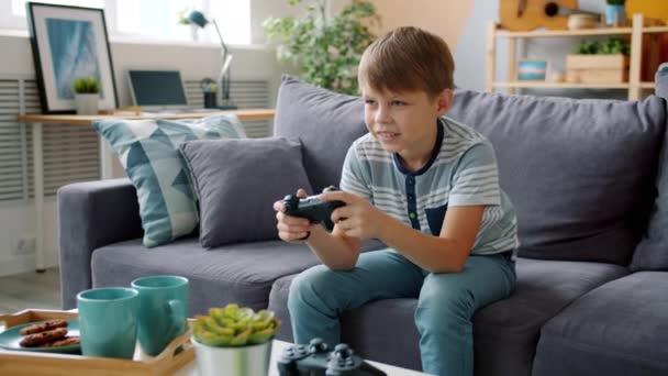 Örömteli gyermek élvezi videojáték apartman szórakozás pihentető kanapén