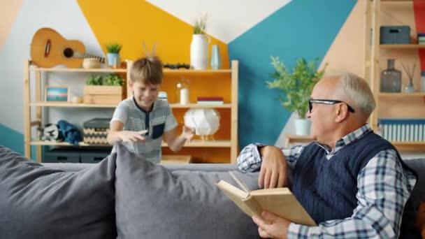 Játékos gyermek és szerető nagyapa csinál pacsit, míg az öreg ember könyvet olvas otthon