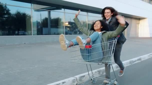 Man and woman riding shopping cart outdoors in city having fun laughing