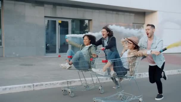 Men pushing shopping carts with women holding smoke flares outdoors