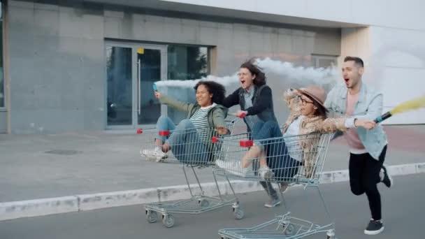 Muži tlačí nákupní vozíky se ženami drží kouřové erupce venku