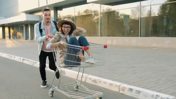 Portrait of girl and guy having fun in city riding shopping trolley laughing