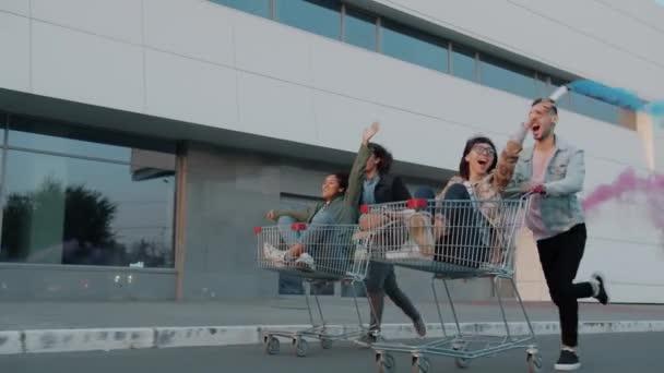 Veselá mládež jezdí na nákupních vozících ve městě ulice drží kouřové erupce