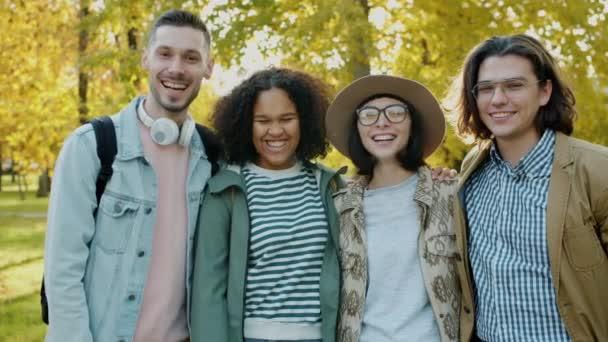 Vidám fiatalok turisták hátizsákkal nevetve a szabadban mosolyogva a parkban