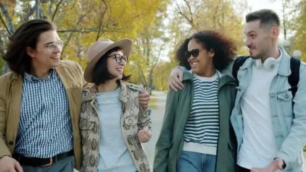 Happy men and women walking in park talking gesturing enjoying communication