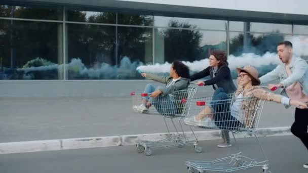Slow motion of happy young people riding shopping carts holding smoke grenades