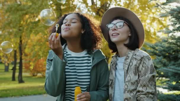 Boldog fiatal nők barátok fúj szappanbuborékok a parkban a napsütéses őszi napon