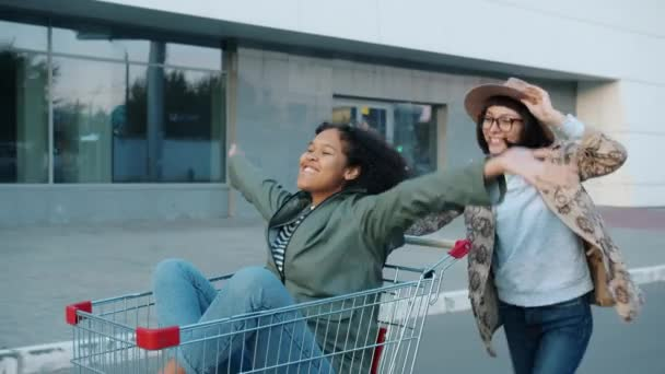 Happy girls friends riding shopping cart laughing outdoors near mall