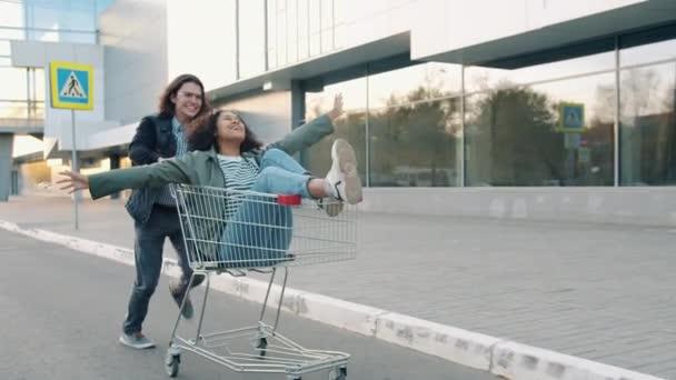 Handsome guy pushing shopping cart with mixed race girl having fun outside
