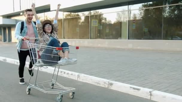 Happy man pushing a shopping cart with excited girl sitting inside having fun in city