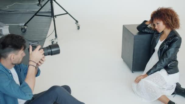 erfolgreiche Fotografin fotografiert attraktive junge Dame in modernem Studio