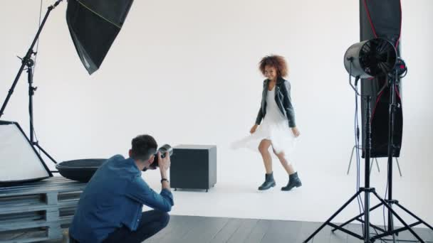 Attractive mixed race lady posing for camera jumping in studio with photographer