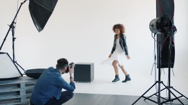 Atraktivní smíšená závodní dáma pózující pro kameru skákání ve studiu s fotografem