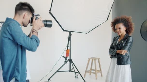 attraktive Frau posiert im Studio, während Fotograf mit Kamera fotografiert