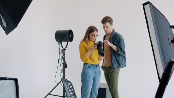 Photographer and model looking through pictures on electronic camera talking in studio