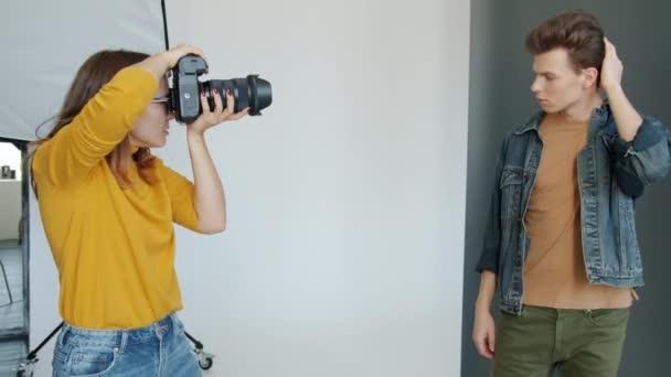 Zpomalení pohybu pohledný chlap módní model pózování pro fotografa uvnitř