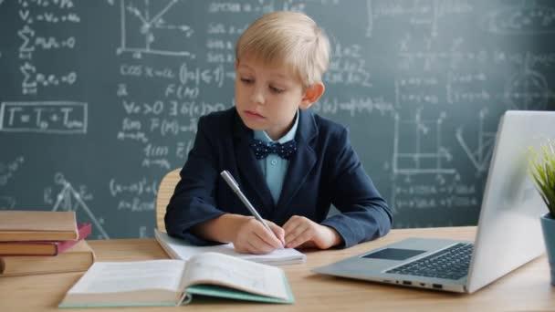 Fiatal zseni tanul tudomány az iskolában írás notebook komoly arc