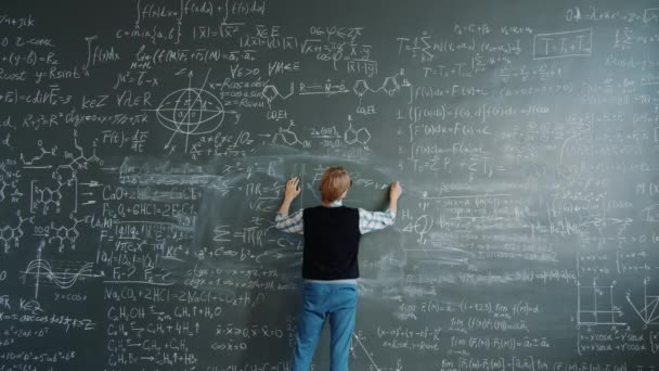 Crazy scientist writing formulas on chalkboard then shouting beating board