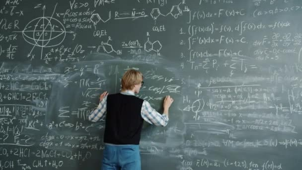 Crazy young man beating chalkboard yelling feeling angry because of science problem