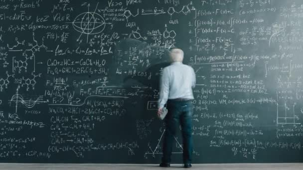 Time lapse of smart mature man professor writing equations on chalkboard