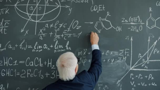 Slow motion of gray-haired man writing formulas on chalk board in college
