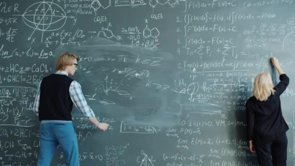 Zpomalení pohybu muže a ženy psaní vzorce na tabuli v univerzitní třídě