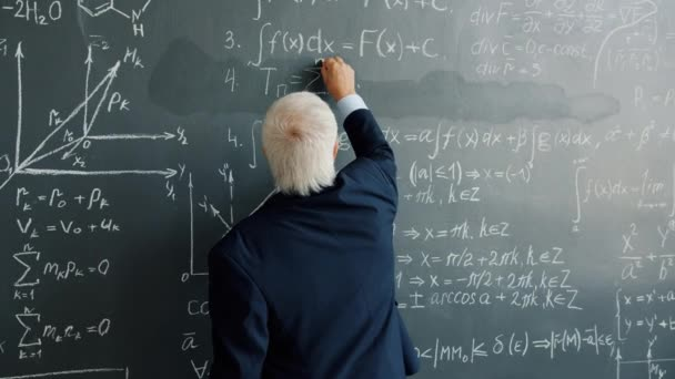 Slow motion of intelligent man in suit writing formulas on blackboard indoors