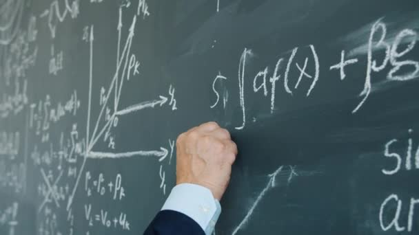 Slow motion of male hand underlining maths equation on chalkboard in class