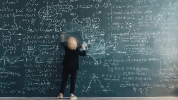 Zoom-in time lapse of intelligent female teacher writing formlas on blackboard