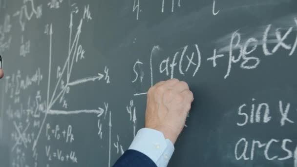 Close-up of male hand with chalk underlining formula on chalkboard in class