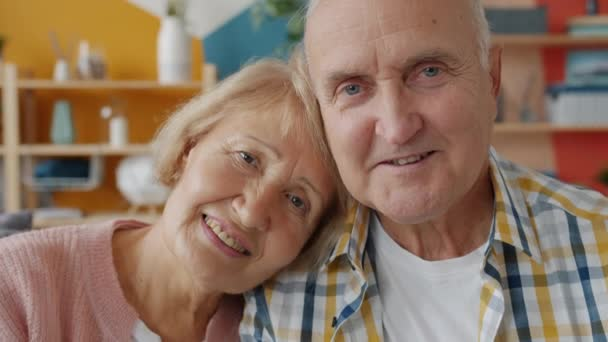Portrait of loving couple elderly woman and man smiling looking at camera at home