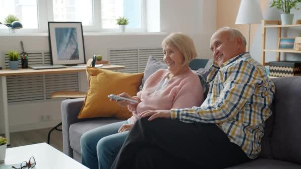Senior Mann und Frau vor dem Fernseher und reden entspannt auf der Couch in der Wohnung