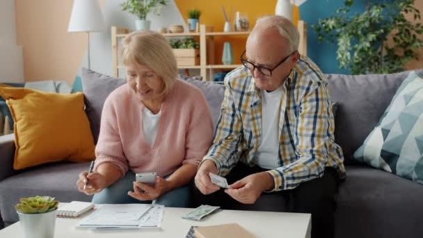 Senior muž a žena počítání peněz prostřednictvím účtů zaneprázdněn s financemi