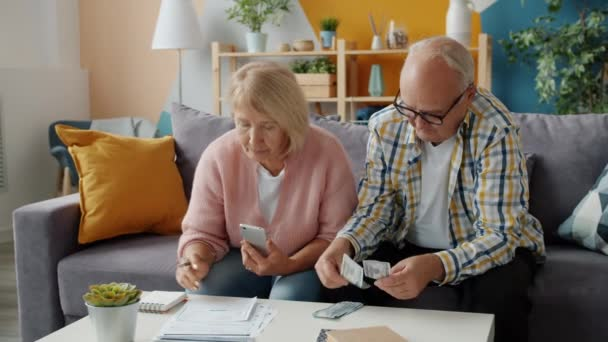 Senior pár zabývající se finančními papíry a počítání peněz v bytě