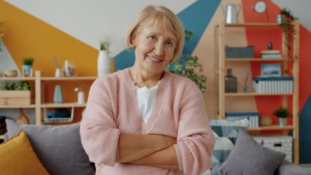 Lassú mozgás idős nő mosolyog nézi kamera álló karok keresztbe otthon
