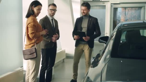 Sales manager discussing car with clients happy couple in auto dealership