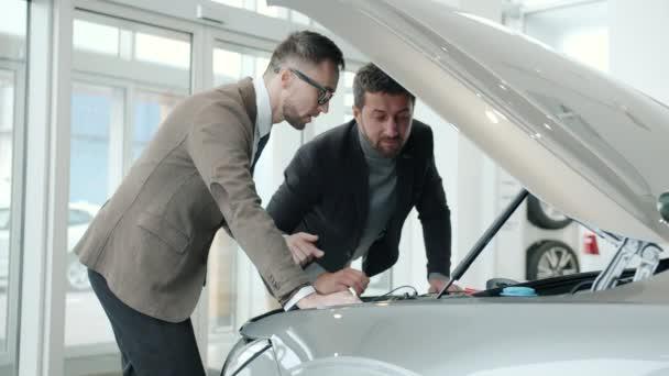Slow motion of car dealer describing engine to buyer in modern showroom talking gesturing