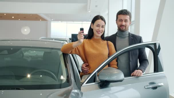 Portrait of happy young couple smiling standing beside expensive car in showroom