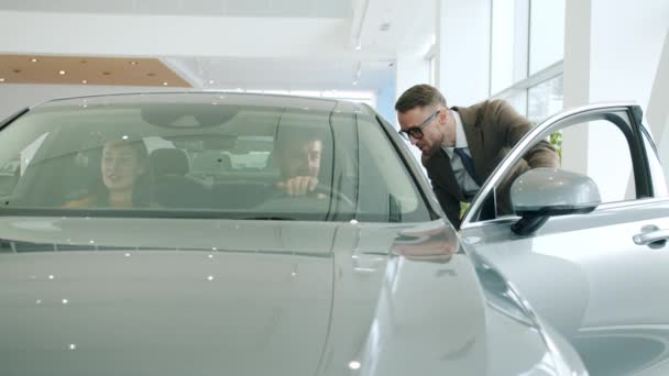 Young family sitting inside car in showroom and discussing deal with manager