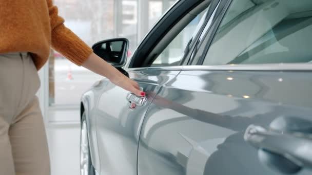 Slow motion of attractive woman opening car door in showroom looking inside
