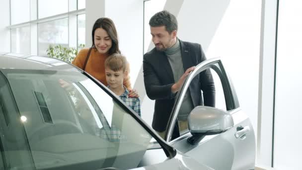 Vidám pár és a gyermek vásárol autót a bemutatóteremben csinál pacsi-öt nyíló auto ajtó