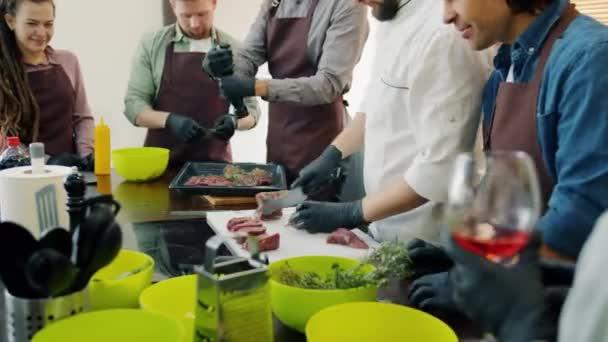 Vielfältige Gruppe glücklicher Menschen in Schürzen beim Kochen in der Küche bei Kochkursen
